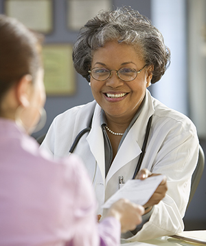 Doctor handing prescription to woman.