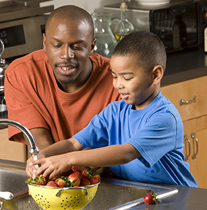 Man and boy washing strawberries in sink.
