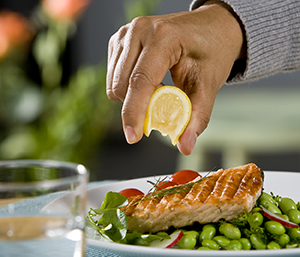 Closeup of man's hand squeezing lemon on broiled salmon.