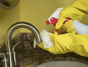 Closeup of gloved hands holding spray bottle and cleaning sink.