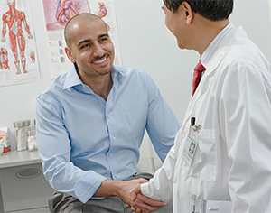 Doctor shaking hands with male patient in exam room.