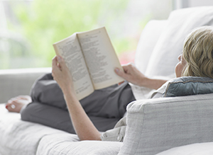 Woman lying on sofa reading a book.