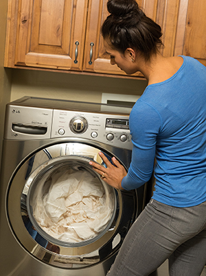 Woman loading sheets into home washing machine.